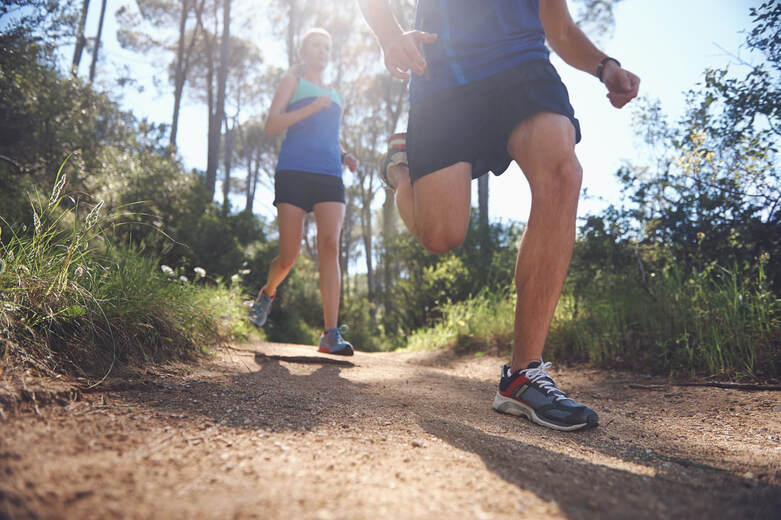 Couple running through the woods, trail running